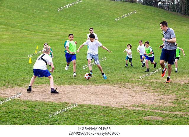 Adults on grassed area with school children supervising a soccer game, Everyone can be seen running and chasing the ball