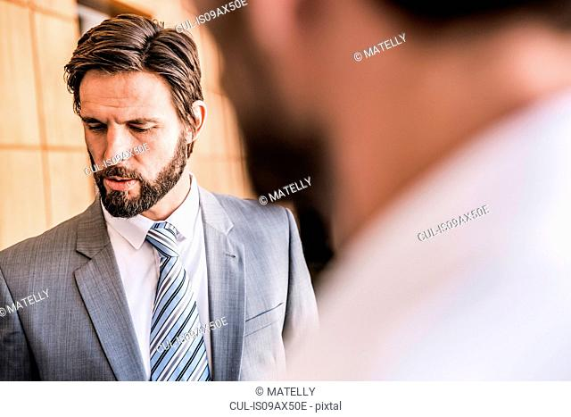 Bearded businessman looking down