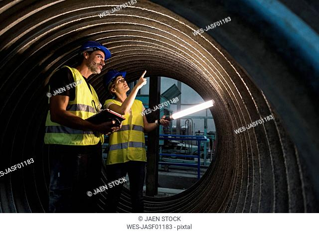 Man and woman examining giant construction tube