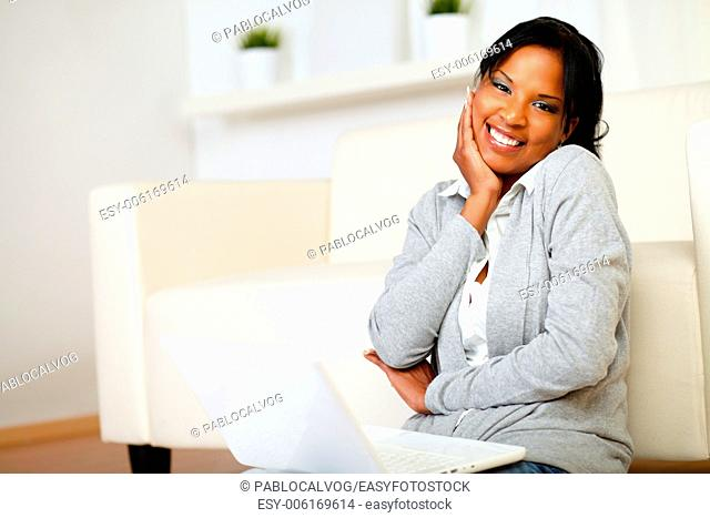 Portrait of a cute black woman smiling at you while is sitting on the floor with laptop
