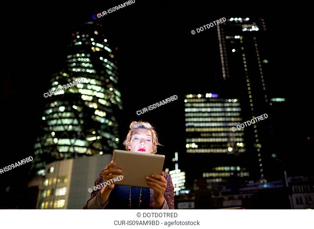 Mature woman in front of office buildings using digital tablet at night, London, UK