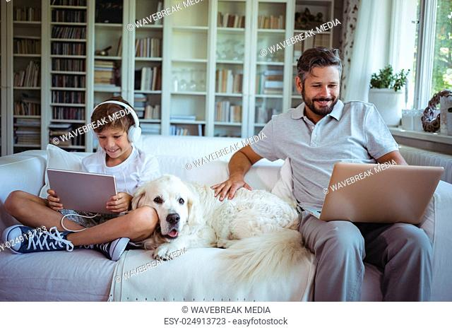 Father and son sitting on sofa and using digital tablet and laptop