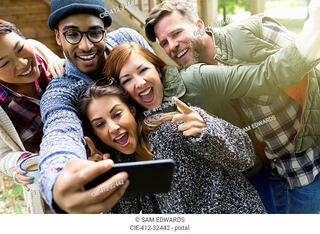 Playful friends with camera phone gesturing taking selfie