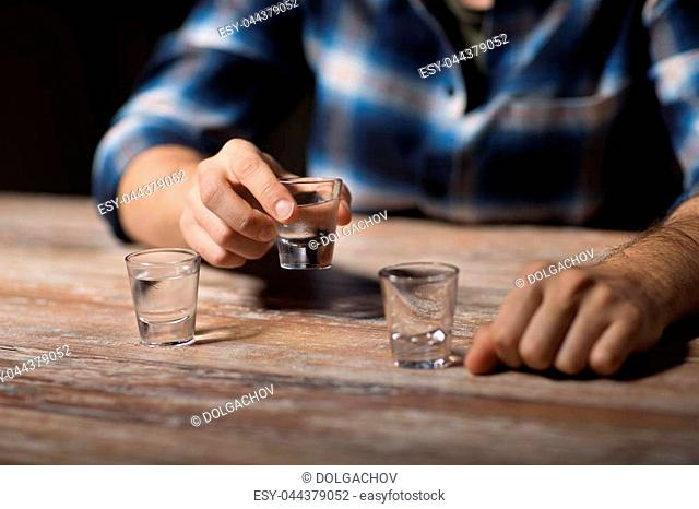alcoholism, alcohol addiction and people concept - hands of male alcoholic drinking vodka shots at night