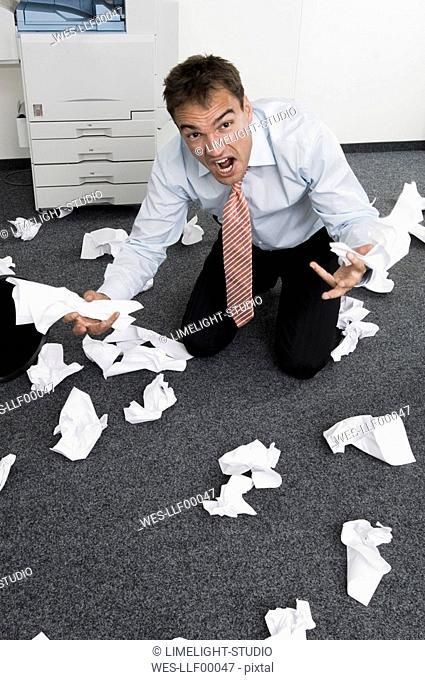 Businessman kneeling among slips of paper, gesturing in despair