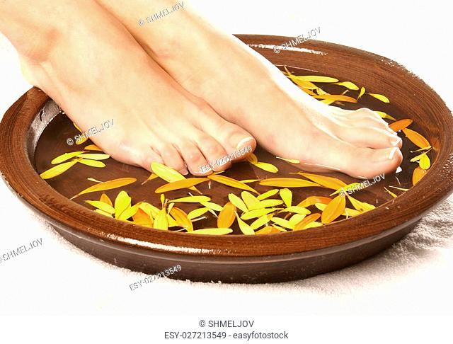 Spa composition of legs, ceramic bowl, towel and petals