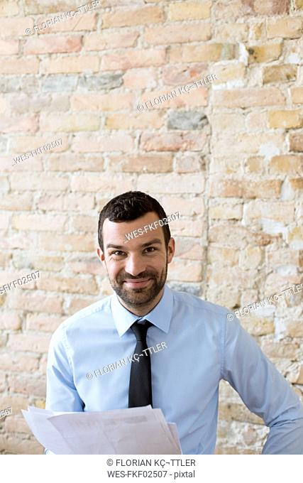 Portrait of smiling businessman with documents at brick wall