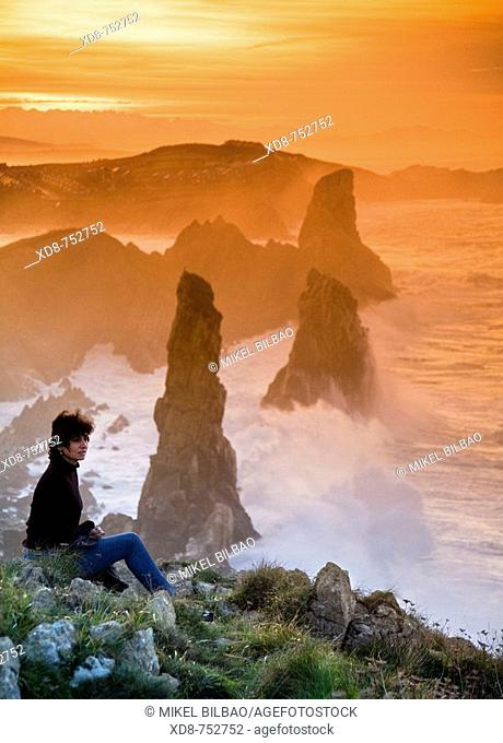 young woman looking from a rocky coast  Liencres, Cantabria, Spain, Europe
