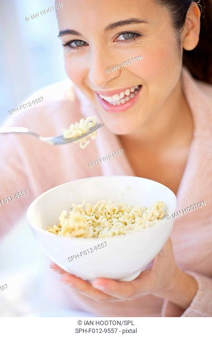 MODEL RELEASED. Woman eating bowl of noodles, smiling