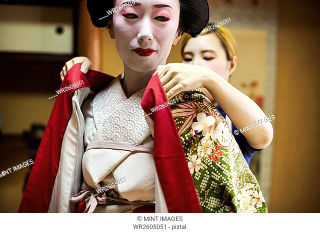 A woman being dressed in the traditional geisha style, wearing a kimono with white face makeup with bright red lips and dark eyes