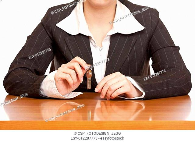 Business woman holds house key for handing over of keys