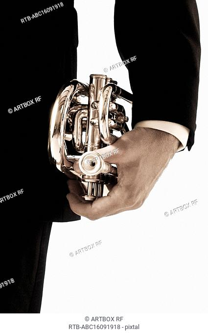Mid section view of a person holding a trumpet