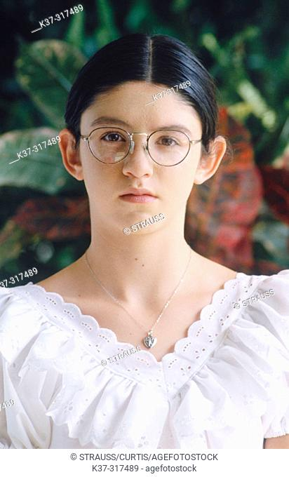 Young hispanic girl wearing white blouse and eyeglasses