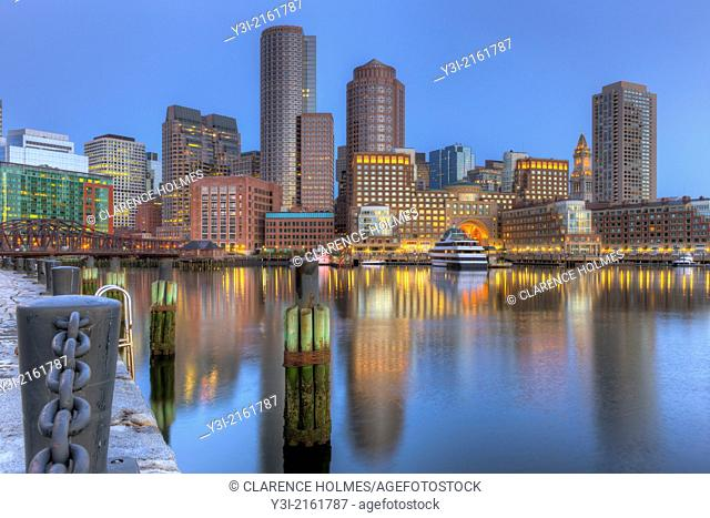 The skyline reflects off the still waters of the harbor in the last hour before sunrise as a new day begins in Boston, Massachusetts, USA