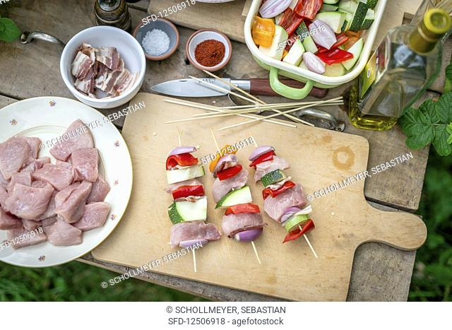 Raw meat skewers with pork, bacon and vegetables on a wooden board