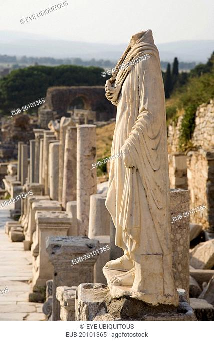 Ephesus. Headless statue on plinth in line of ruined pillars and empty pedestals in antique city of Ephesus on the Aegean sea coast