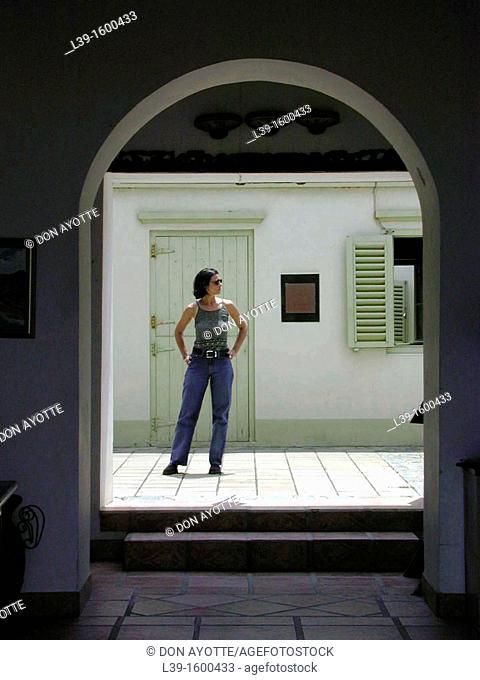 Woman posing in the sun, beyond an archway in Aruba