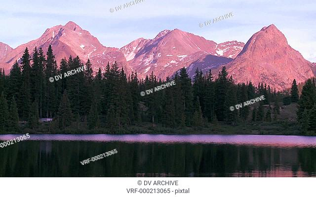 The Rocky Mountains are perfectly reflected in an alpine lake at sunset or dawn