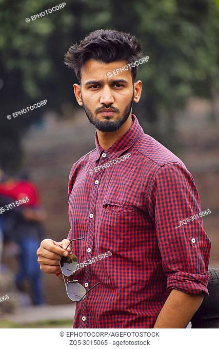 Young man with checked shirt posing with sun glasses, Pune, Maharashtra