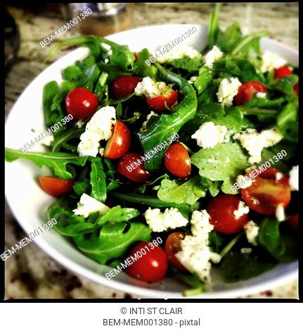 Close up of arugula, goat cheese, and tomato salad