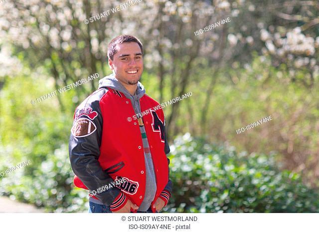 Portrait of high school senior wearing jacket in park