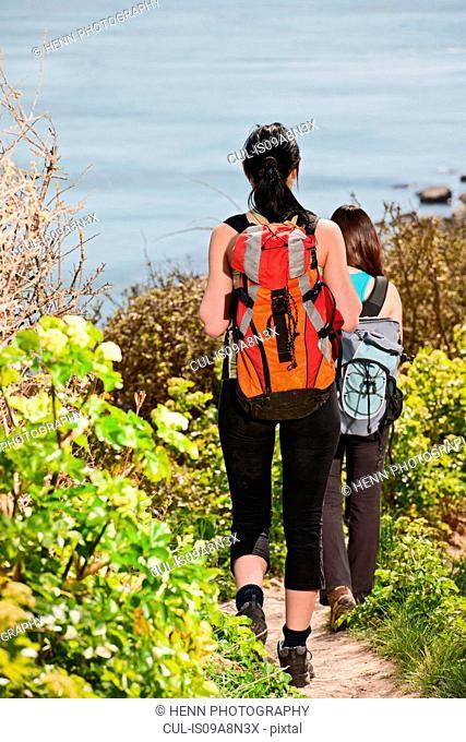 Two female friends walking down coastal path