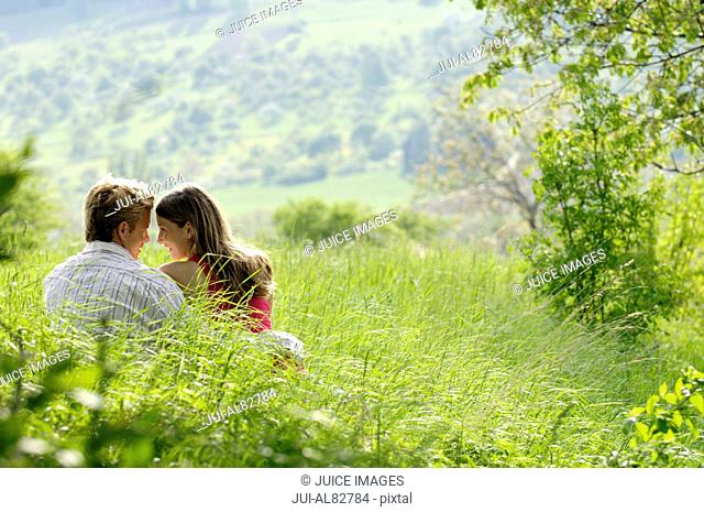 Couple touching foreheads and sitting in grass on hillside
