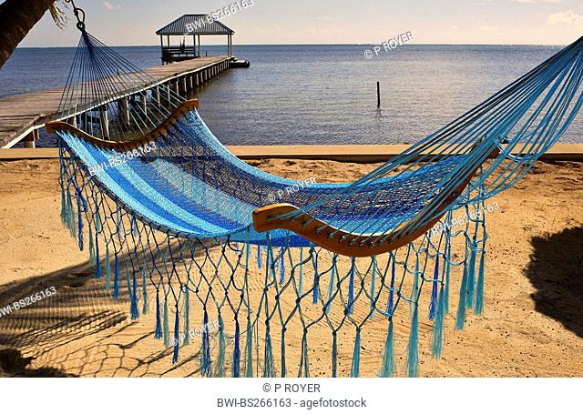 view from the sand beach over a hamock at a wooden footbridge leading into the sea, Belize, Ambergris Caye