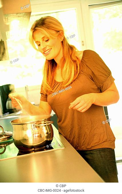 Young Woman InThe Kitchen Cooking Pasta