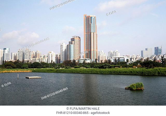 View of wetland habitat with encroaching highrise buildings, looking towards Shenzhen, Lok Ma Chau Nature Reserve, New Territories, Hong Kong, China, May