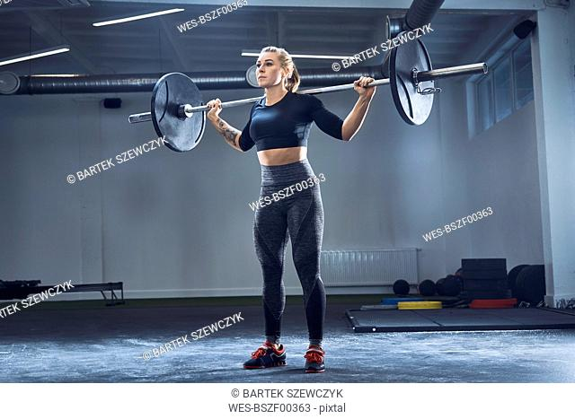 Woman practicing barbell squat at gym