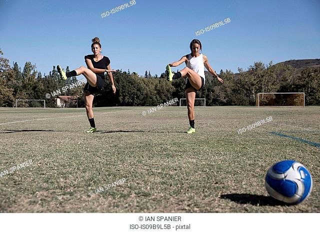 Women on football pitch warming up, stretching legs