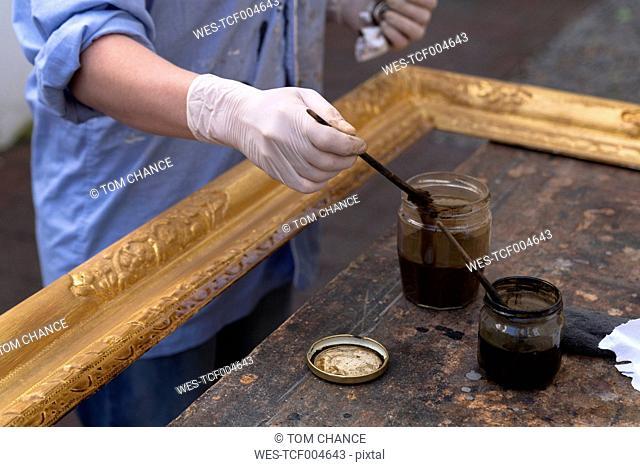 Frame-maker in workshop patinating Baroque wooden frame