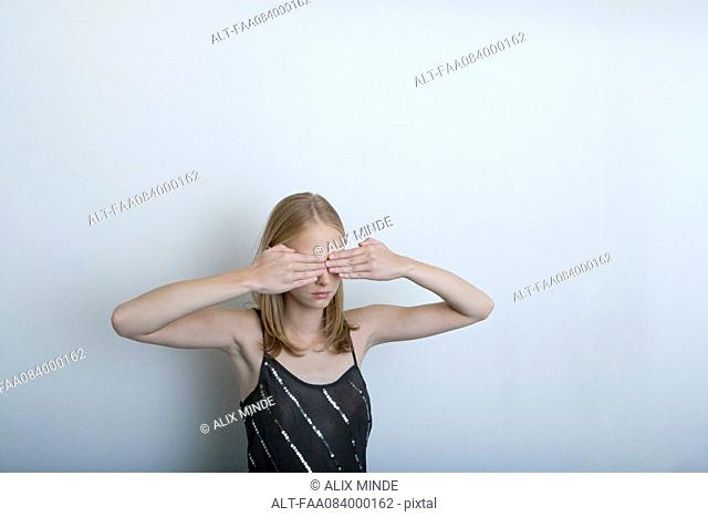 Young woman with hands covering eyes