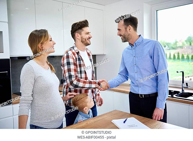 Family and real estate agent shaking hands in kitchen of new apartment