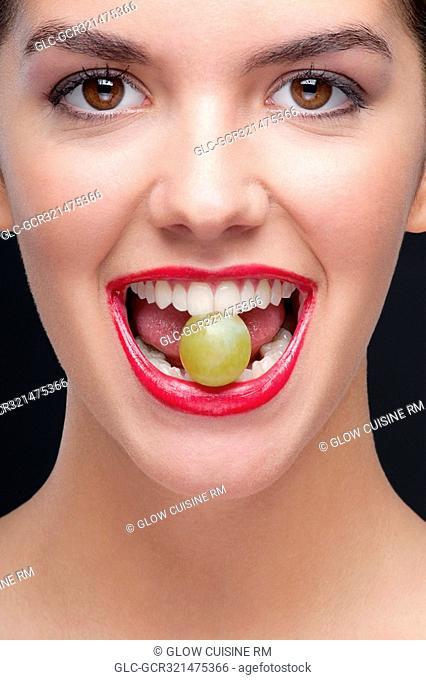 Woman holding a green grape between her teeth
