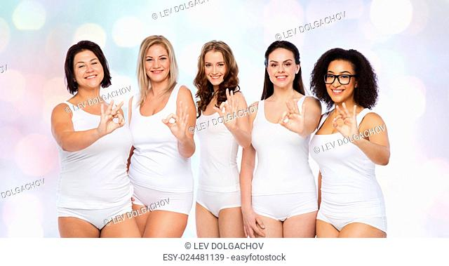 gesture, friendship, beauty, body positive and people concept - group of happy different women in white underwear showing ok hand sign over holidays lights...