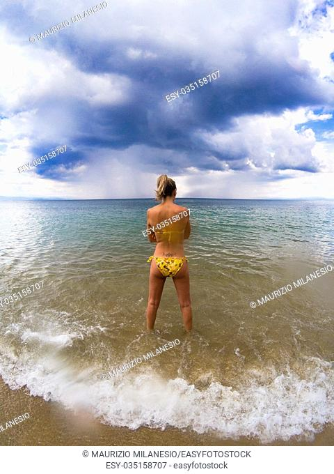 Young girl in bikini, watching from the beach the storm approaching, in the dark sky there are threatening clouds
