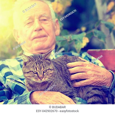 Senior man hugging and cuddling his tabby cat on bench in courtyard