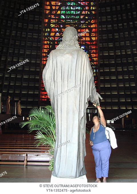 Woman touching the hand on the Statue of Christ, San Sebastion Cathedral interior, Rio de Janeiro, Brazil