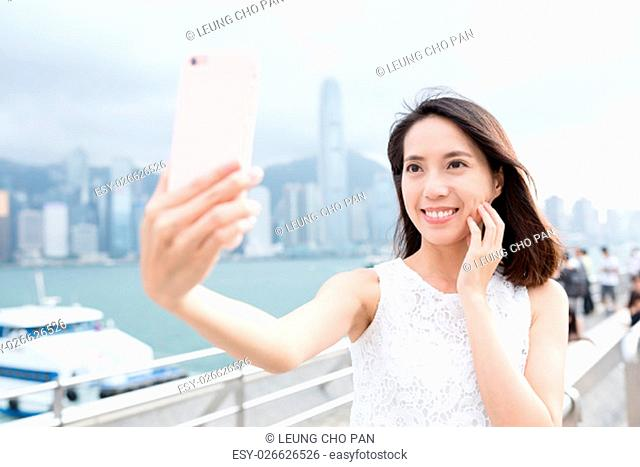 Woman using mobile phone for taking selfie