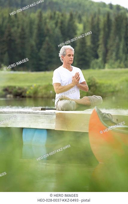 senior man meditating in lotus position on deck