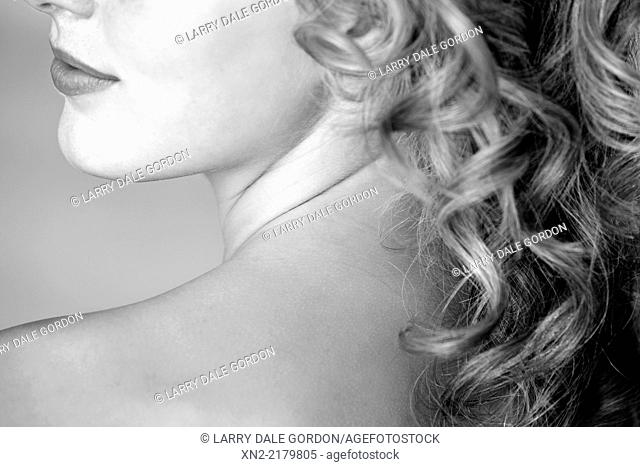 Close-up of a woman in black and white with bare shoulder, neck, lower face and long curly hair