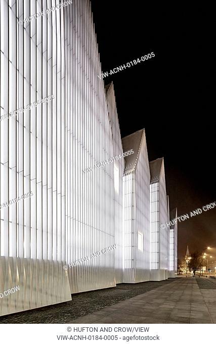 Szczecin Philharmonic Hall, Szczecin, Poland. Architect: Studio Barozzi Veiga, 2014. Night elevation of glowing, illuminated facade in perspective
