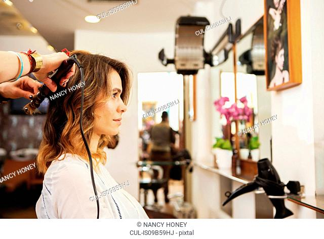 Hairdresser using curling tongs on customer's long brown hair in salon