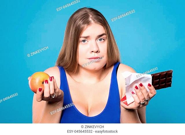 What to choose. Close up of beautiful confused plump girl holding apple and chocolate against isolated blue background
