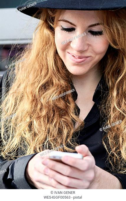 Mid adult woman wearing black hat and using smartphone