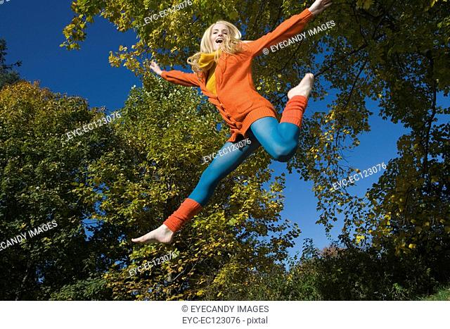 Portrait of young happy woman leaping in air on autumn day