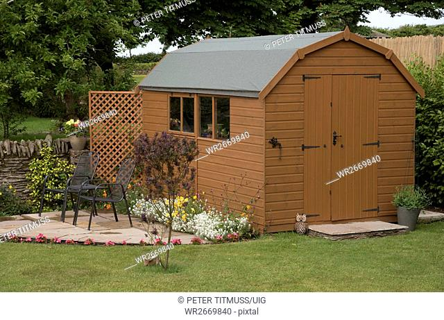 Devon England Uk, Barn Style Garden Shed With A Small Patio And Chairs