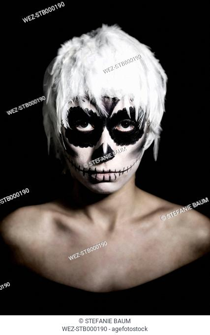 Portrait of woman with skull make-up wearing headgear of white feathers, studio-shot